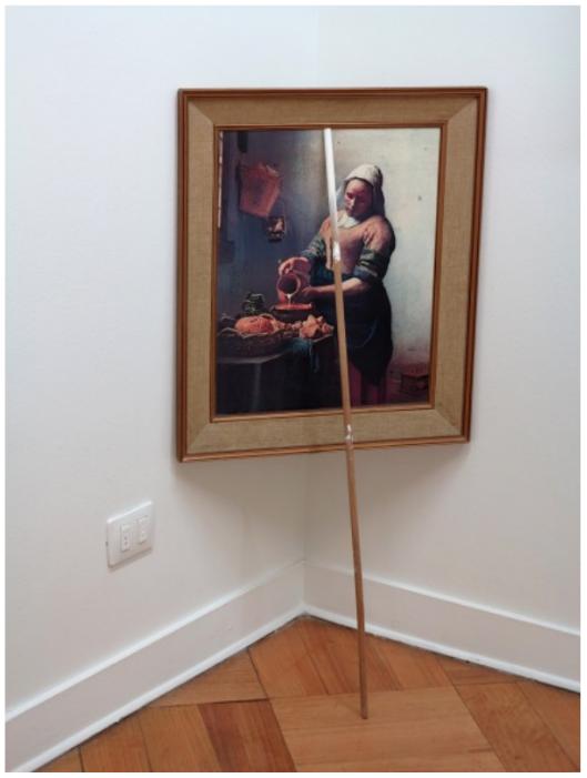 Marco Montiel-Soto, Lechera sostenida por un palo manchado de blanco en la punta, 2013. De Melkmeid, una mala réplica de la pintura del holandés Johannes Vermeer, fue encontrada en la calle. La pintura está dispuesta en equilibrio en una de las esquinas de la galería con la ayuda de un palo de madera encontrado (manchado con pintura blanca en la punta). La leche que sale de la jarra y la mancha blanca en el palo es el gesto al cual hace referencia esta pieza